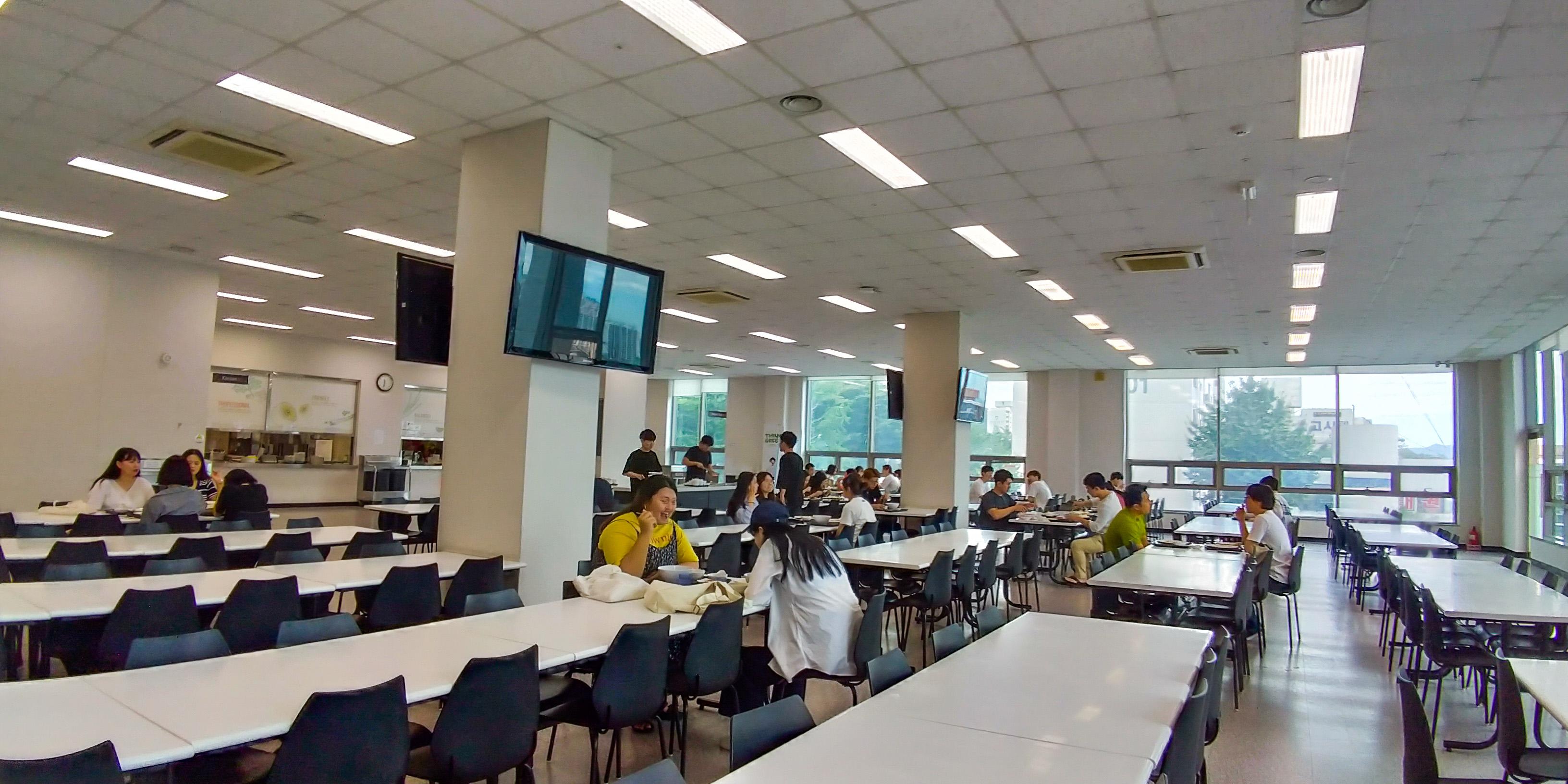 Suasana cafeteria dormitory. Mahasiswa memesan menggunakan mesin lalu mengambil sendiri makanan, side dish, dan minuman. Kemudian memisahkan peralatan makanan kotor pada tempatnya setelah selesai