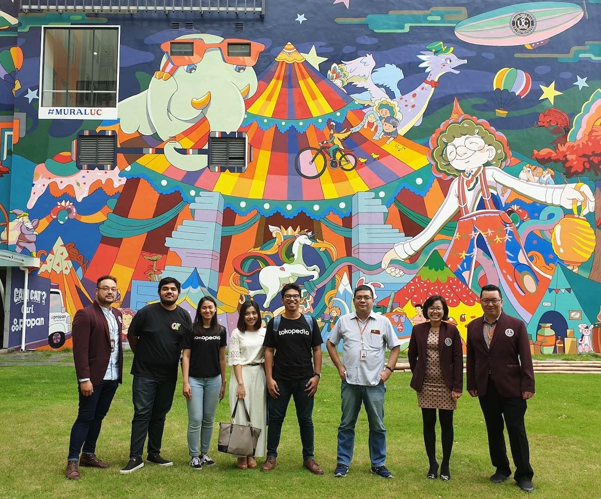 Tokopedia team berfoto bersama dosen dan staff Universitas Ciputra di depan Mural UC